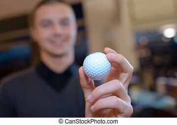 hand of a man holding a golf ball