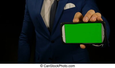 Hand of a man holding a green screen smart phone and pointing with finger at display