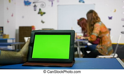 Hand of a man holding tablet pc with green screen in a...
