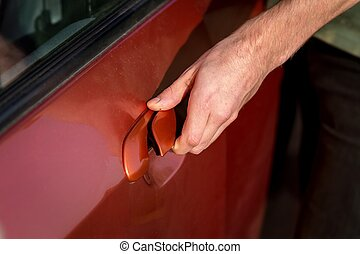 Hand of a man opening car door
