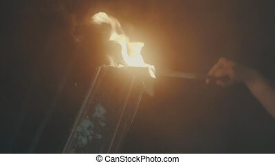 Hand of a man setting fire to the log, with the help of a torch. Fire close up