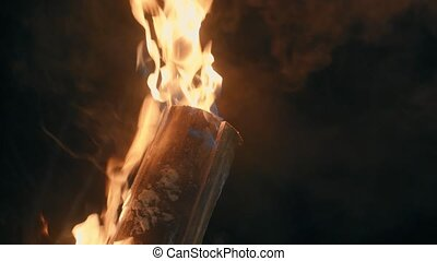 Hand of a man setting fire to the log.