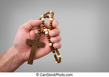 Hand of a religious man holding a dark brown cross