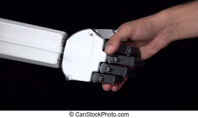 Hand of a robot and a man's hand in one handshake. Black...