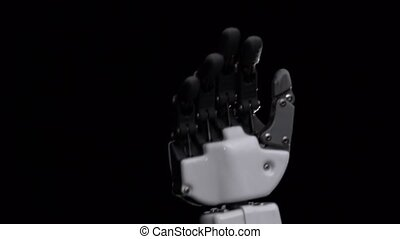 Hand of a robot close up waving goodbye. Black background....