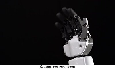 Hand of a robot close up waving goodbye. Black background -...