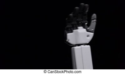 Hand of a robot close up waving hello . Black background