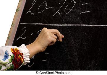 hand of a schoolgirl writing on the chalkboard