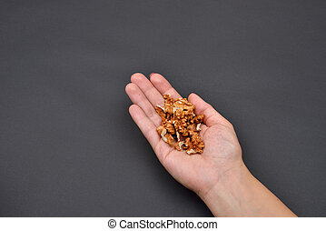 Hand of a woman holding a pile of peeled walnuts isolated on black background. Spice. Taste. Cooking. Food and beverage flavoring