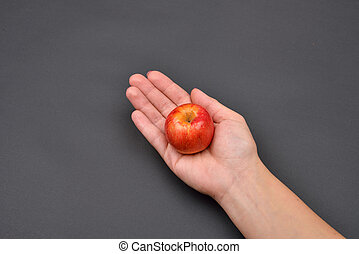 Hand of a woman holding a red fresh apple isolated on black background. Vegetarians and fresh fruit