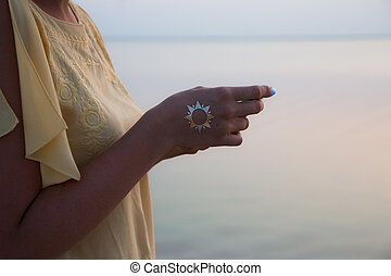 hand of a woman meditating in a yoga pose on the beach at sunset