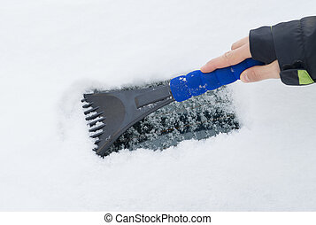 hand of a woman Scraping snow and ice from the car windscreen