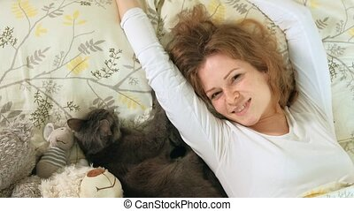 Hand of a woman stroking gray cat sleeping on the bed