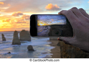 Hand of an adult man on vacation taking photos with a mobile pho
