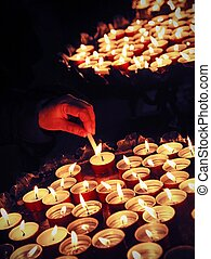 hand of an elderly woman hand lighting a candle during the Holy