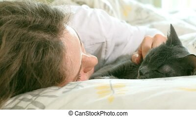 Hand of an elderly woman stroking gray cat sleeping on the bed