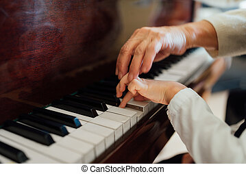 hand of an experienced pianist  helping young students