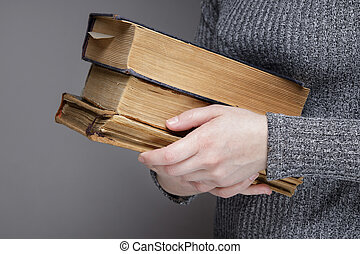 hand of an invisible person holds hugs an old book.