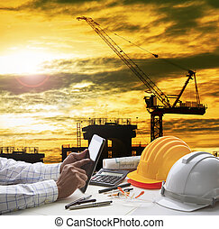 hand of architect working on computer tablet  with construction industry and engineer working tool on top of table against home out line and sketching of modern building perspective