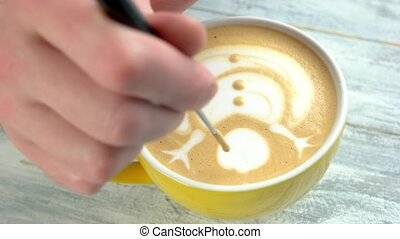 Hand of barista, latte art. Snowman picture on coffee foam.