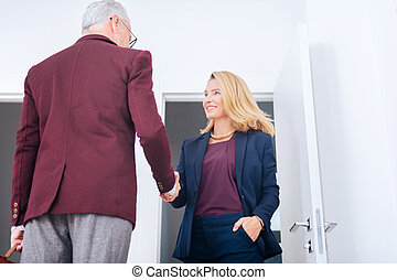 Stylish elegant businesswoman wearing nice necklace shaking hand with her boss
