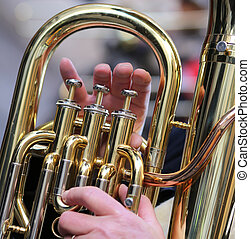 hand of boy plays the trombone in the brass band