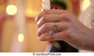 Hand of Bride with Ring and Candle in Church