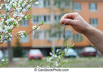 Hand of broker holding key to a dream house