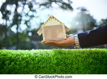 hand of business man and wood house model on beautiful green...