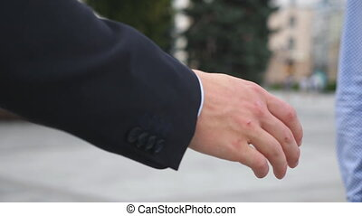 Hand of business man passing a black briefcase to his partner. Colleagues shake arms outdoor with blur city at background. Biz meeting of two young businessmen. Close up Slow motion