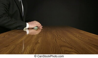 Hand of business man puts a wad of money on an office desk