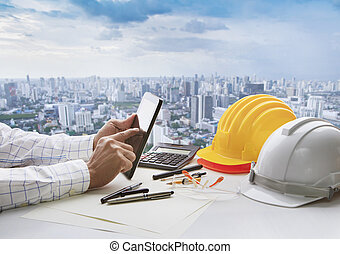 hand of business man touching on computer tablet screen and safety helmet on working table against cities of high building background