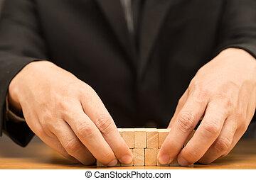 Hand of businessman arrange wood piece