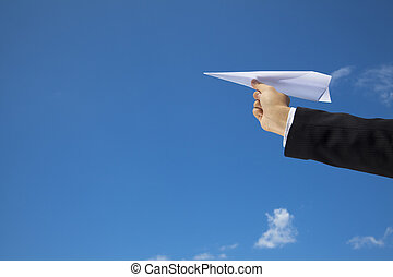 hand of Businessman letting an airplane made of paper fly...