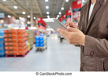 Hand of Businessman, Manger use Mobile Tablet in supermarket