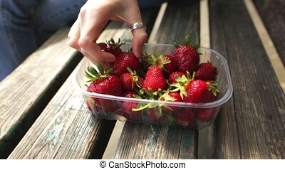 Hand of caucasian woman takes a strawberry from a box of fresh ripe fruits.