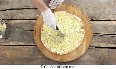 Hand of chef cutting pizza. Baked vegetarian food.