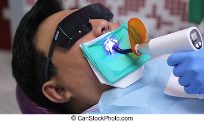 Hand of dentist holding an LED lamp in oral cavity of patient with glasses from ultraviolet.