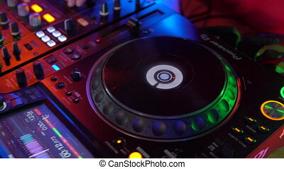 Hand of Dj on the mixing console twist turntable. Slide down...