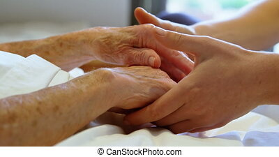 Hand of doctor reassuring to senior woman at home 4k -...