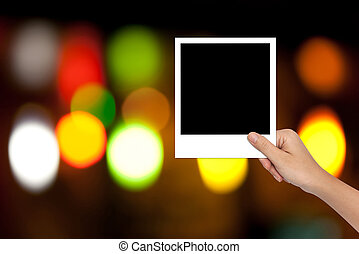 Hand of Female Holding a Blank photo frame on colorful bokeh bac