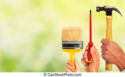 Hand of handyman with a hammer and screwdriver.