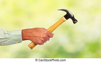 Hand of handyman with a hammer.