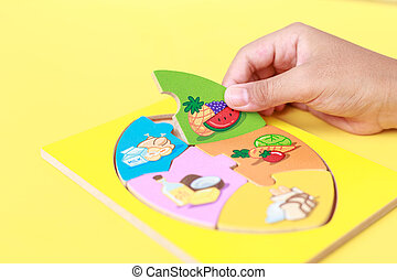 Hand of kid holding wooden jigsaw of the 5 food Groups. Child development concept