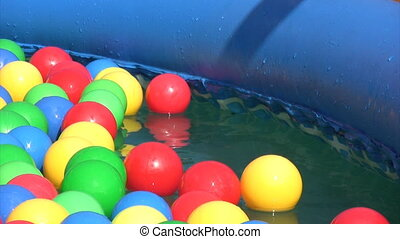 hand of kid picking up balls floating in inflatable water pool