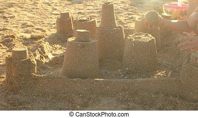 Hand of kid, sandcastle.