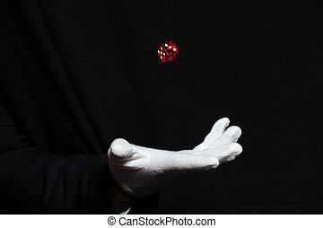 Hand of magician in white glove showing tricks with dice