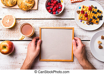Hand of man holding empty picture frame. Breakfast meal.