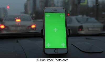 hand of man holding mobile smart phone with chroma key green screen in car