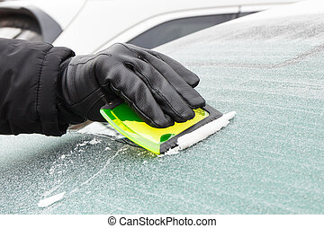Hand of man in leather glove scraping ice from car windscreen